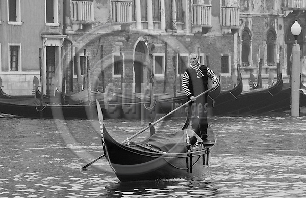 Venice-Italy - January 09, 2011 -- A gondoliere / gondolier starting his day early in the morning on Grand Canal / Canal Grande on his gondola -- tourism, infrastructure, transport, water, b&w -- Photo: Horst Wagner / eup-images