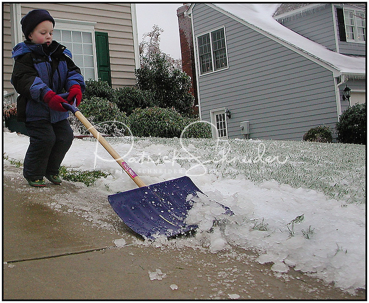 A young boy helps to shovel his family's driveway during a light snowfall in Charlotte, NC. Model released image.