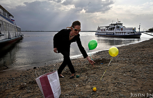 Youngsters with ballons stroll in Russian Khabarovsk city on the bank of the Amur River. The Amur runs along the border separating Russia and China and is a major transport route between the two countries.