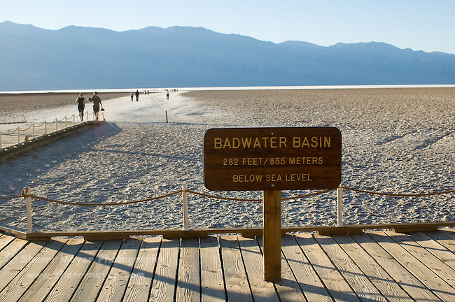 Badwater Basin sign and visitors walking on the salt flats at Badwater Basin, Death Valley National Park, California