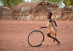 A boy rolls part of a truck wheel through the Yida refugee camp in South Sudan. Some 53,000 refugees from Sudan's Nuba Mountains live in the camp, with an equal number living in two nearby camps.