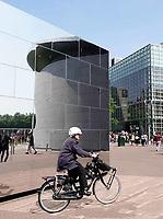 Nederland - Amsterdam - 2018.   Vrouw met fietshelm fietst op het Museumplein. Weerspiegeling van het van Gogh Museum.   Foto Berlinda van Dam / Hollandse Hoogte.