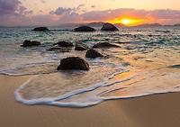 Virgin Gorda, British Virgin Islands, Caribbean<br /> Boulders awash in the surf of Little Trunk Bay near the Baths. Setting sun over Tortola across Sir Francis Drake Channel.
