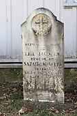 Old tombstone in grave yard of  the parish of Cap Sante,  Sacre Coeur de Jesus Catholic church