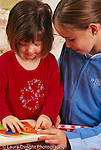 2 year old toddler girl helped with geometric puzzle by sister age 11