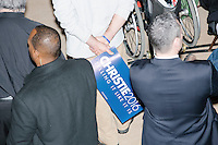 A man holds a campaign sign while listening as Republican presidential candidate and New Jersey governor Chris Christie speaks at his final New Hampshire town hall of the primary election at the St. George Greek Orthodox Cathedral in Manchester, New Hampshire, on Mon., Feb., 8, 2016.