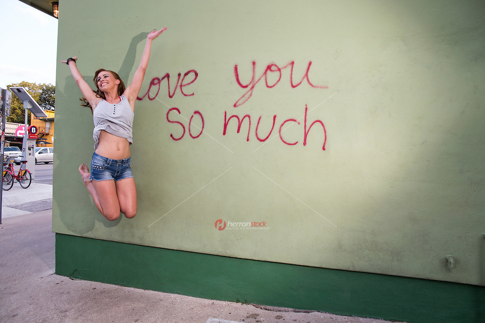 """Playful local South Austin woman jumps for joy at the """"i love you so much"""" mural on South Congress Ave. (SoCo)."""