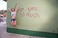"Playful local South Austin woman jumps for joy at the ""i love you so much"" mural on South Congress Ave. (SoCo)."