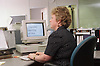 Woman with visual impairment sitting at desk in office using computer,