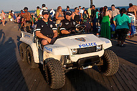 NYPD members ride a small vehicle on Coney Island Boardwalk in New York city borough of Brooklyn, Sunday July 31, 2011. Built in 1923 and officially named The Riegelmann Boardwalk, Coney Island Boardwalk is located along the southern shore of the Coney Island peninsula adjacent to the Atlantic Ocean.
