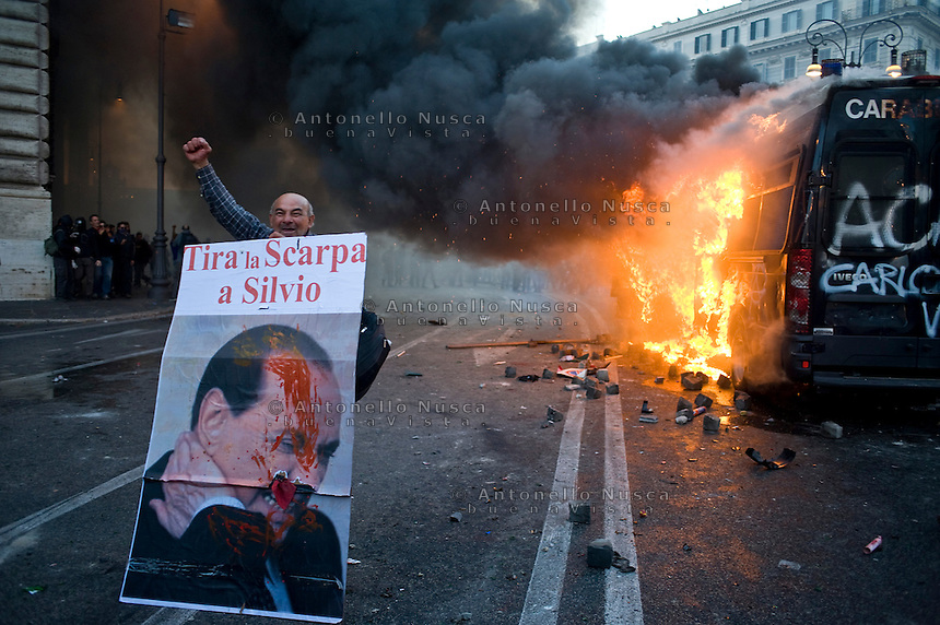 Un manifestante mostra fiero il suo cartello mentre un veicolo dei Carabinieri brucia in Piazza San Giovanni.<br /> A demonstrator holds a poster reading 'throw a shoe at Silvio' as a vehicule of Carabinieri is set on fire in the city centre