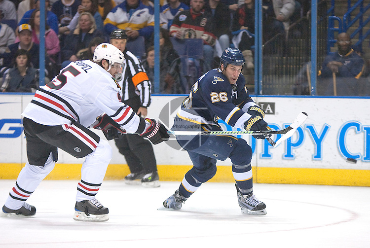 January 2,  2010                            Blackhawks player Brent Sopel (5, left) chases after St. Louis Blues right wing B.J. Crombeen (26) who passes the puck off in the second period behind the Blackhawks goal.  The St. Louis Blues hosted the Chicago Blackhawks on Saturday January 2, 2010 at the Scottrade Center in downtown St. Louis.