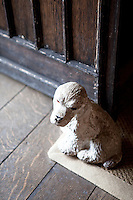 A stone statue of a dog acts as a doorstop