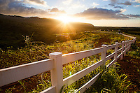 Beautiful sunset behind mountains with sun rays hitting lush hills and a white picket fence, North Shore, Oahu.