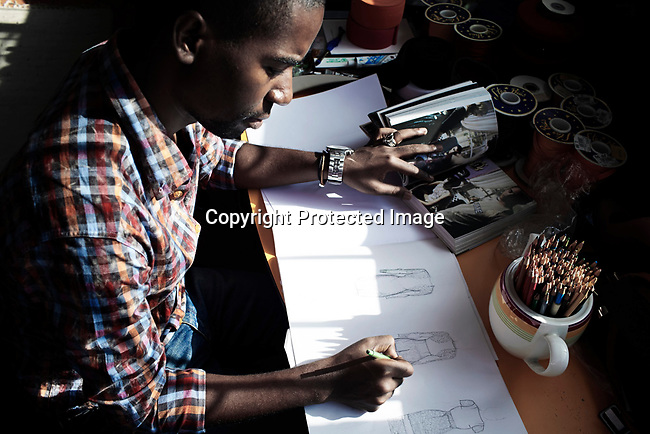 MAPUTO, MOCAMBIQUE - JUNE 27: The fashion designer Taibo Bacar draws new dresses in his studio on June 27, 2013 in Maputo Mozambique.Taibo is one of the youngest and most celebrated African designers and he has shown his designs around Africa and the world. (Photo by: Per-Anders Pettersson)