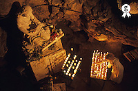 France, Provence, Sainte-Baume Mountain, woman burning candle at Troglodyte Sainte-Marie Madeleine Holy Cave (Licence this image exclusively with Getty: http://www.gettyimages.com/detail/sb10066226y-001 )