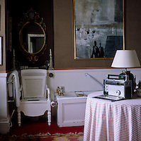 The bathroom has an old-fashioned commode as a toilet and a figurative painting by Anthony Fry hanging above the bath
