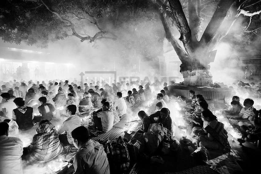 The faithful pray while thick clouds of incense raise into the air in front of Shri Shri Lokenath Brahmachari Ashram temple for the Kartik Brati or Rakher Upobash religious festival in Barodi,  Near Dhaka, Bangladesh