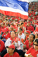 Thailand. Bangkok. Red-shirted supporters of ousted premier Thaksin Shinawatra gather outside Government House to demand the dissolution of the House of Representatives and the resignation of the Democrat led coalition. Thousand of anti-government Democratic Alliance against Dictatoship (DAAD) protesters shout slogans while demonstrating. Each day by late afternoon, the red-shirt uprising swells witj thousand supporters to hear verbal attacks against the government. A new political crisis with the red power political movement.  A thai flag floats in the air. The flag of the Kingdom of Thailand shows five horizontal stripes in the colours red, white, blue, white and red, with the middle blue stripe being twice as wide as each of the other four. The three colours red-white-blue stand for nation-religion-king, an unofficial motto of Thailand. The flag was adopted on 28 September 1917, according to the royal decree.  29.03.09 © 2009 Didier Ruef