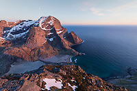 Storskiva mountain peaks rises over Bunes beach in light of the midnight sun, Moskenesøy, Lofoten Islands, Norway