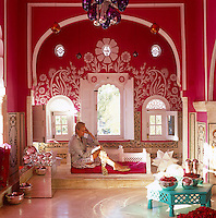 Liza Bruce relaxes in front of the ornately-painted window recesss in the airy sitting room of her colourful and flamboyant apartment