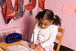 Education Preschool 3-4 year olds pretend play area girl sitting at desk and writing squiggles and circles horizontal