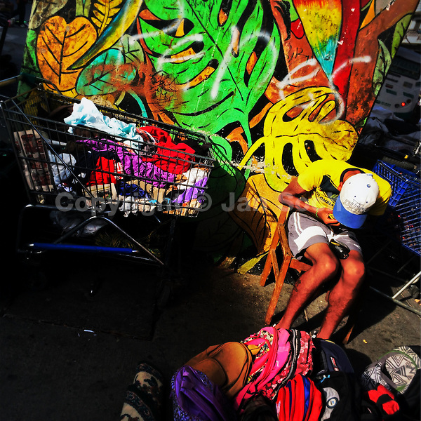 A young Colombian man sells worn clothes in a daily flea market underneath the elevated metro track in the center of Medellín, Colombia, 23 November 2016.