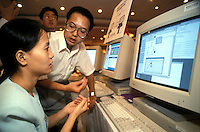 A salesman demonstrates a computer to a young woman in Guangzhou, China.