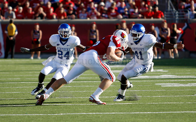 Defensive linemen Randal Burden and Mychal Bailey stop a louisville player in the second half of the UK's 23-16 win over U of L, kicking off Joker Phillip's reign as head coach on Saturday, September 5, 2010. Photo by Britney McIntosh | Staff