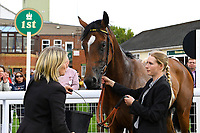 Winner of The Smith & Williamson Fillies' Novice Stakes (Div 1) Motivate Me ridden by Jack Mitchell and trained by Roger Varian  with Lass in the Winners enclosure  during Afternoon Racing at Salisbury Racecourse on 16th May 2019