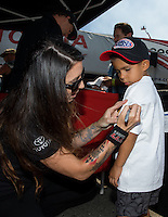Jul. 26, 2013; Sonoma, CA, USA: NHRA funny car driver Alexis DeJoria signs an autograph during qualifying for the Sonoma Nationals at Sonoma Raceway. Mandatory Credit: Mark J. Rebilas-