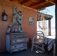 The wall of the porch is decorated with a home-made rustic artwork