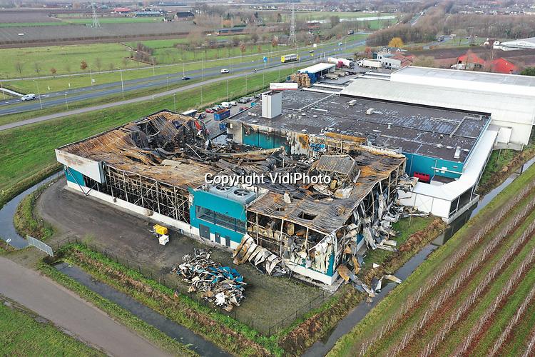 Foto: VidiPhoto<br /> <br /> KESTEREN &ndash; Bij het uitgebrande koelbedrijf van Van Soest Coldstores in Kesteren, is dinsdag begonnen met de opruimwerkzaamheden. Niet alleen op het bedrijf zelf, maar ook in de nabije omgeving worden door wind en rook meegevoerde stukken dakbedekking en andere resten opgeruimd. De miljoenenbrand brak vrijdag uit in plastic kratten in de vriesruimte, aldus de veiligheidsregio Gelderland-Zuid. De N233 tussen de A15 en Rhenen moest door de enorme rookontwikkeling afgesloten worden. Bij de brand zijn geen schadelijke stoffen vrijgekomen en er vielen geen slachtoffers. Twintig brandweerauto&rsquo;s rukten uit om de megabrand te bestrijden. Vanuit de lucht is de enorme schade goed te zien.