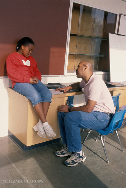 Berkeley, CA  African American fifth grade teacher having serious discussion with student in hall outside classroom