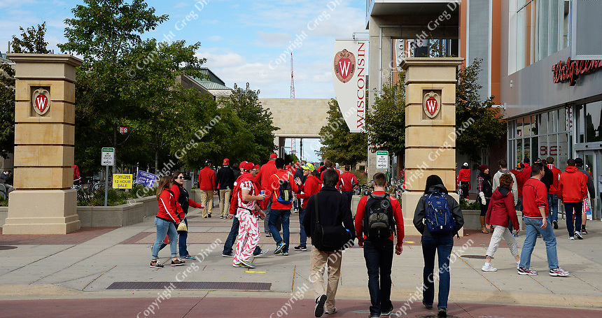 University of Wisconsin Badger Fans walk through East Campus Mall on Saturday, October 3, 2015 in Madison, Wisconsin