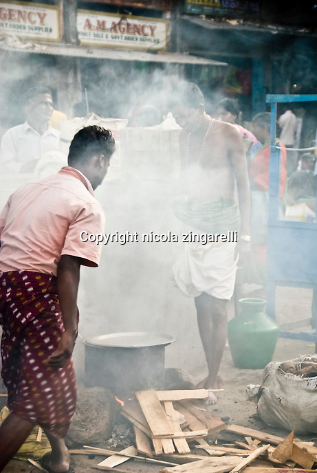 Port Blair, Andaman Islands. Middle aged indian man cooking something on a stove in the street with a lot of smoke