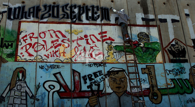 Foreign activist paints graffiti on a separation barrier during a protest calling for a Palestinian state with full UN membership at the Qalandia checkpoint between the West Bank city of Ramallah and Jerusalem, Saturday, Sept. 17, 2011. Portrait on the left represents the late Palestinian leader Yasser Arafat. Photo by Issam Rimawi