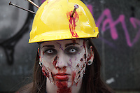 Female participant in the prague zombi walk in may 2014, photographed as a headshot, wearing a yellow builders helmet with 3 nails hammered into it, having blood in the face.