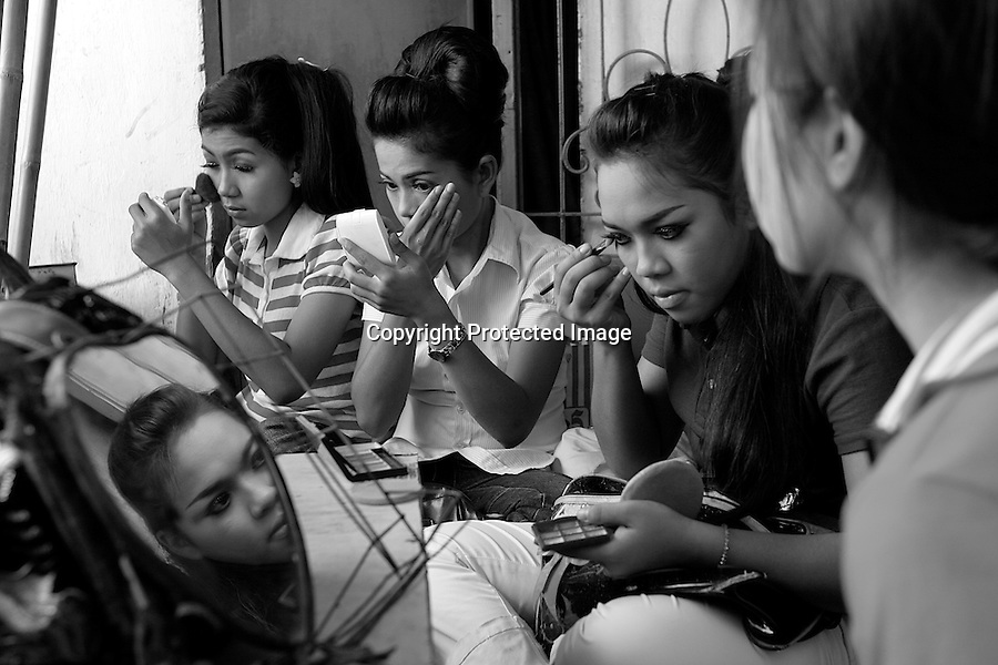 Children of Bassac. Before performing in a restaurant, the young women of Ieng Sithul's association are doing their make up in a room situated on the third floor of the building, a slum in the center of Phnom Penh, Cambodia - 2008