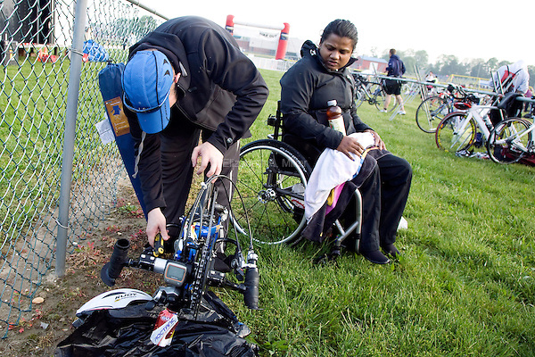Shawn sets up Minda's handcycle and racing wheelchair while Minda looks on in the bicycle and running transition area before the start of the New Jersey Devilman Triathlon on May 5, 2012 in Cumberland County, New Jersey.