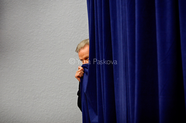 Actor John Voight peeks out behind the stage where U.S. Presidential hopeful Rudy Giuliani (R-NY) was about to speak at a rally with him and former FBI director Louis J. Freeh at the Fantasy of Flight museum in Polk City, Florida, on Sunday, January 20, 2008. (Photo by: Yana Paskova for The New York Times)..Assignment ID: 30055282J............