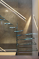 Recessed down lighters illuminate the metal handrails on the staircase walls, while fibre-optics light up the treads