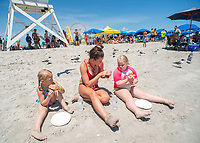 From left, Veronica Praweckyj, 6, lifeguard Grace Comas, 17, and Sage Praweckyj, 8, have pizza for lunch during the 11th annual 21 Down Beach Day Monday, July 15, 2019 at Schellenger Street beach in Wildwood, New Jersey. Every summer, the Wildwood Beach Patrol opens Lincoln Ave Beach for kids with down syndrome and their families for 21 Down Beach Day. Often, kids with down syndrome aren't comfortable in the ocean. Their parents can't just relax and watch them frolic. But on July 15th, the kids swim with seasoned Wildwood lifeguards on soft-top paddle boards. (Photo by William Thomas Cain / CAIN IMAGES)