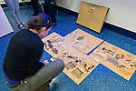 "Hempstead, New York, U.S. 12th November 2013.  A student studies the original drawings of Janet Hamlin, at back in black pants, a courtroom artist covering the military tribunals at Guantanamo Bay since 2006, who showed and discussed her work at Hofstra University. Much of the time Hamlin was the only journalist providing a visual record of the events at the United States naval base in Cuba, and her new book ""Sketching Guantanomo"" is a collection of her images."