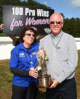May 19, 2014; Commerce, GA, USA; National Dragster photographer Teresa Long poses with NHRA official Graham Light with the Wally trophy reserved for the next lady professional racer to reach the 100 win milestone the Southern Nationals at Atlanta Dragway. Mandatory Credit: Mark J. Rebilas-USA TODAY Sports