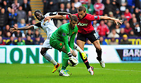 Swansea's Nathan Dyer kept off the ball by defencer Nemanja Vidic.<br /> Saturday 17 August 2013<br /> Pictured: <br /> Re: Barclays Premier League Swansea City v Manchester United at the Liberty Stadium, Swansea, Wales