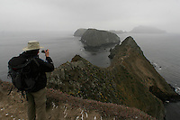 ANACAPA,CA - May 05, 2008: A hiker take in the view of middle and west anacapa islands as seen from inspiration point on east Anacapa Island, May 5, 2008. Anacapa,a small but dramatically jagged island 12 miles off the coast, part of the Channel Islands National Park is five miles long and 1/4 mile wide.