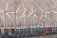 A Union Pacific container train runs past wind turbines generating electricity on the San Gorgonio Pass Wind Farm serving Palm Springs, California.