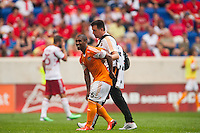 Corey Ashe (26) of the Houston Dynamo is helped off the field. The New York Red Bulls defeated the Houston Dynamo 2-0 during a Major League Soccer (MLS) match at Red Bull Arena in Harrison, NJ, on June 30, 2013.