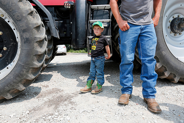 Jayden Dammann, 3, waits for a tractor ride while his father, Justin, visits with others on the family farm in rural Page county on July 19, 2014.  Justin says he feels confident about the management of the family farm one day passing on to Jayden.